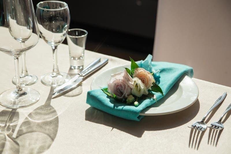 Serviette аквамарина с оформлением цветка лежа на плите обедающего стоковое изображение