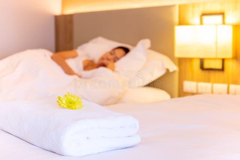 Serviette avec la fleur sur le lit dans la chambre d'hôtel avec la femme dormant à l'arrière-plan image stock