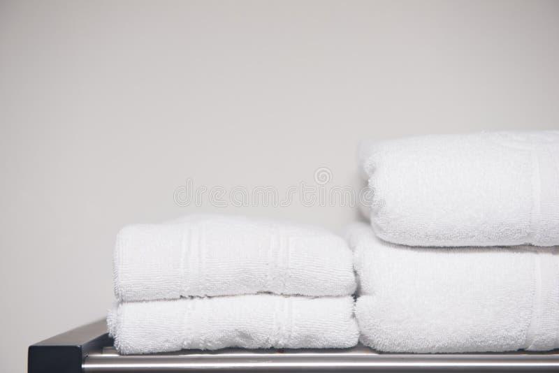 Serviette blanche placée sur des étagères dans la salle de bains de l'hôtel photo stock