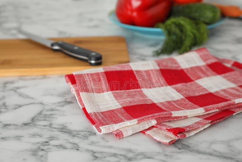 Serviette de cuisine à carreaux sur la table de marbre blanche photos stock