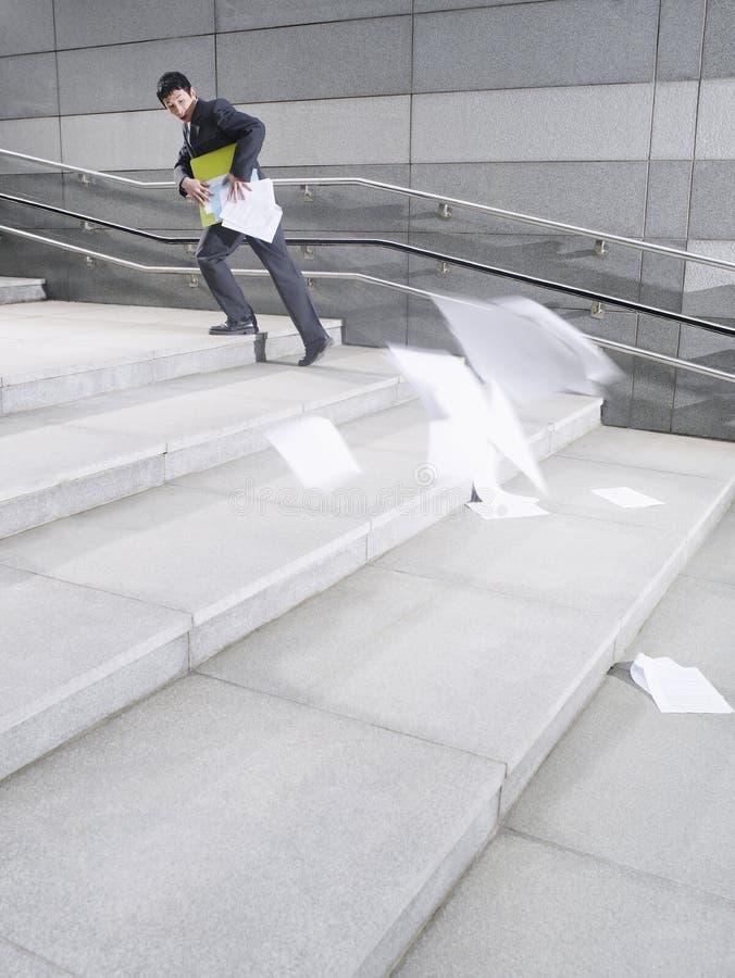 Serviette de Losing Papers From d'homme d'affaires tout en marchant vers le haut des étapes photos libres de droits
