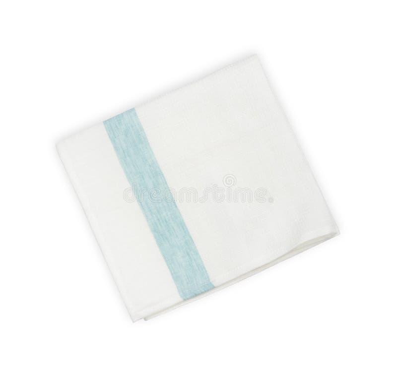 Serviette de toile pliée avec la ligne bleue d'isolement sur le fond blanc images stock