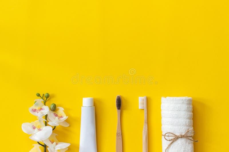 Serviette des brushses e et tube en bambou qui respecte l'environnement naturels de pâte dentifrice et de fleur d'orhid pour lav images libres de droits