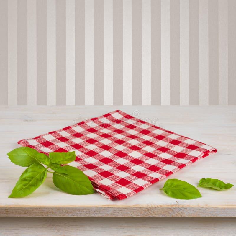 Serviette et feuilles à carreaux rouges sur la table au-dessus du fond de vintage photos stock