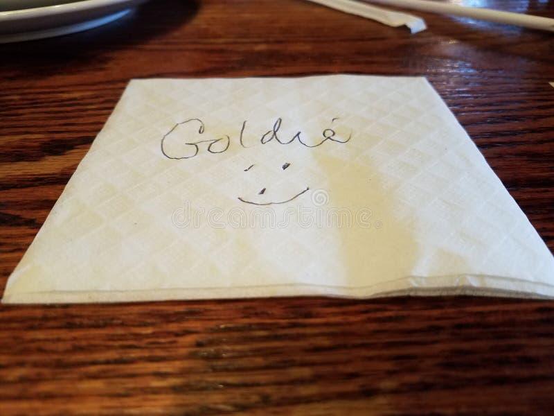 Serviette mit dem Namen Goldie und ein Gesicht auf Tabelle lizenzfreie stockbilder
