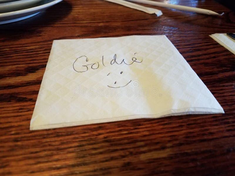 Serviette mit dem Namen Goldie und ein Gesicht auf Tabelle lizenzfreies stockbild