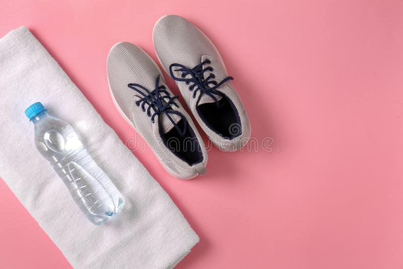 Serviette molle propre avec les chaussures de sports et la bouteille de l'eau sur le fond de couleur photos libres de droits