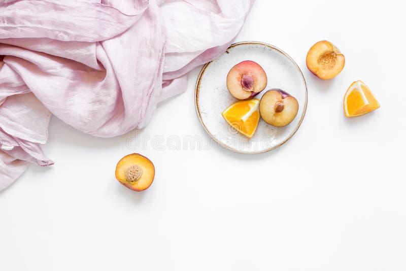 Serviette, pêche coupée et orange pour le fruit exotique sur la maquette blanche de vue supérieure de fond photographie stock libre de droits