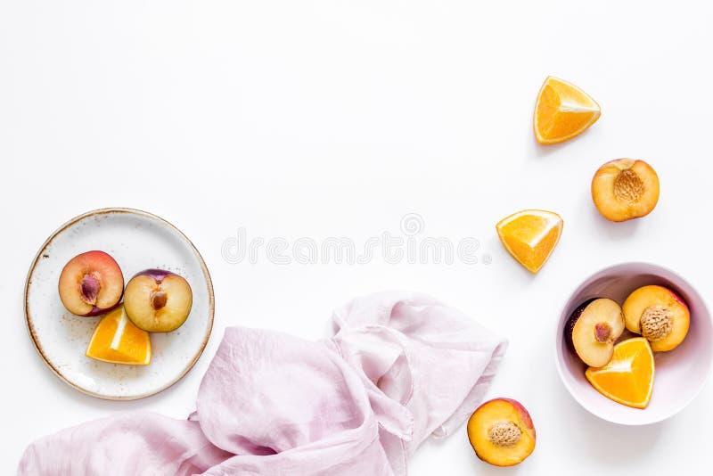 Serviette, pêche coupée et orange pour le fruit exotique sur la maquette blanche de vue supérieure de fond photos libres de droits