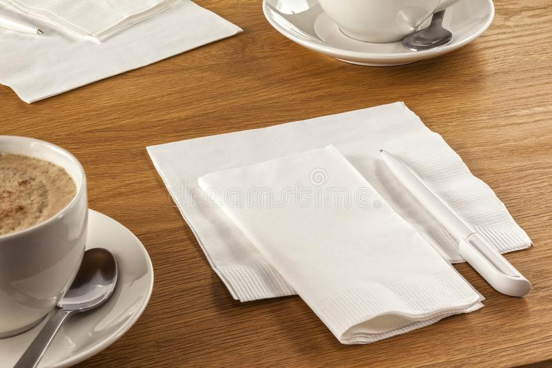 Serviette and Pen on a Desk. Serviette and Pen - napkin or serviette and pen on table, ready to make a note of your latest great idea, along with a cup of coffee royalty free stock image