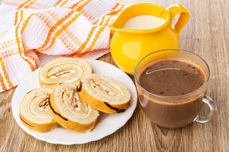 Serviette, Scheiben der Schweizer Rolle in der Platte, Krug Milch, Kakao mit Milch in der Schale auf Holztisch stockbilder