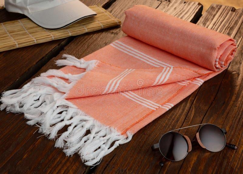 Serviette turque de coton de hammam tissé sur métiers à main orange sur le pilier en bois photo libre de droits