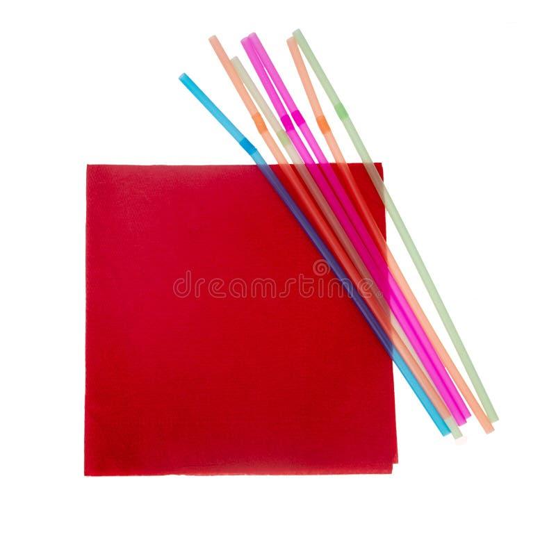 Serviette vermelho e palhas bebendo flexíveis plásticas isolados no branco imagens de stock