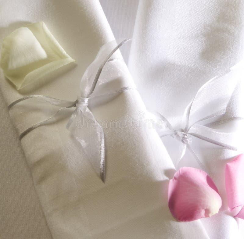 Servietten und rosafarbene Blumenblätter lizenzfreies stockfoto