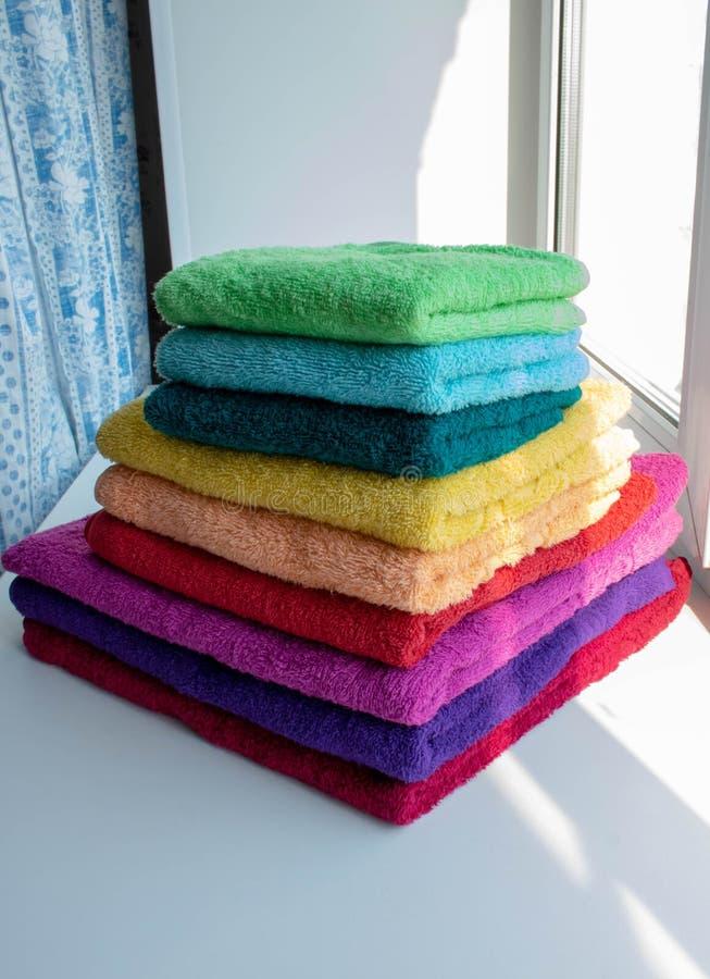 Serviettes éponge multicolores dans une pile sur la fenêtre image libre de droits