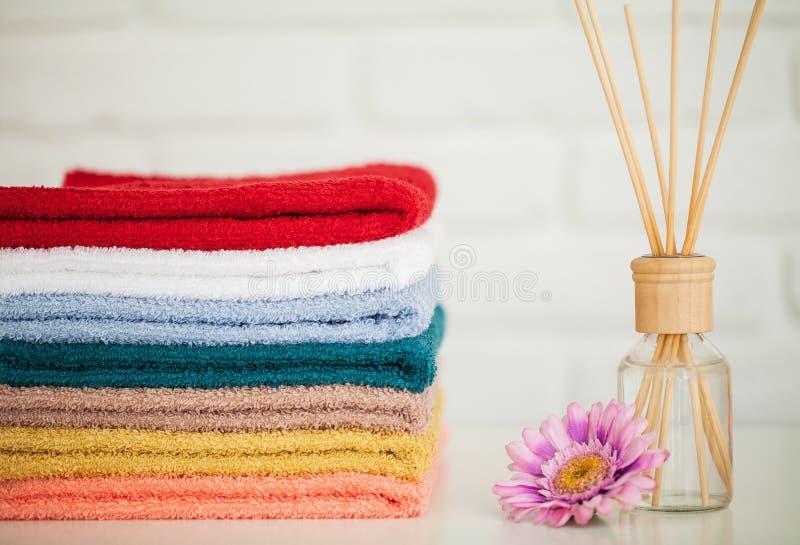 Serviettes de bain pelucheuses sur la table en bois légère avec des bâtons d'arome images libres de droits
