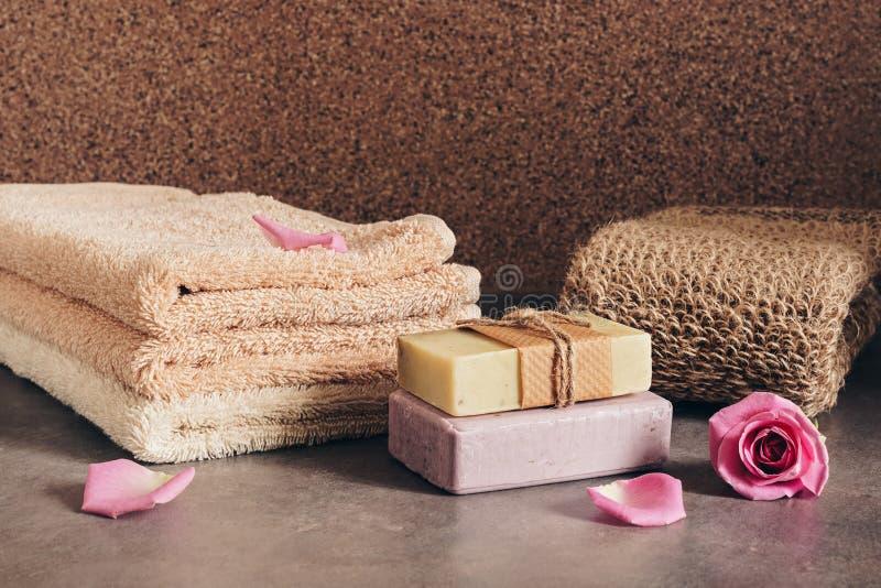 Serviettes de bain, savon fait main, éponge de loofah et pétales de rose Ensemble d'accessoires de bain et de spa photo stock