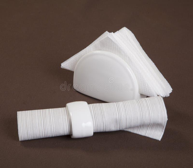 Serviettes de papier et de tissu pour la table serviettes de restaurant pour un arrangement élégant de table sur un fond brun photos libres de droits