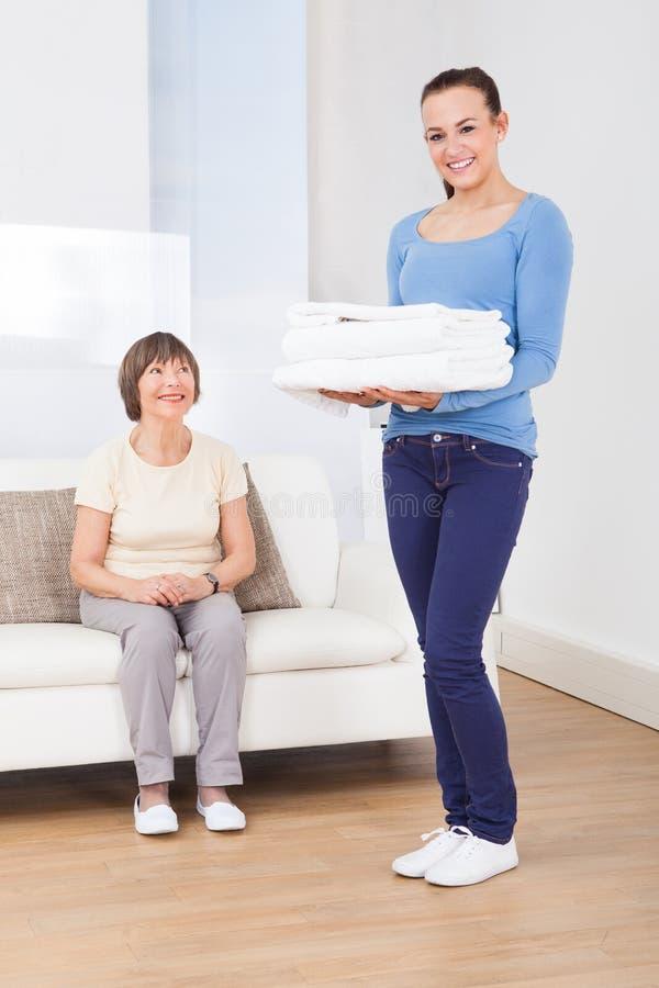 Serviettes de transport de gardien avec la femme supérieure s'asseyant sur le sofa photos libres de droits