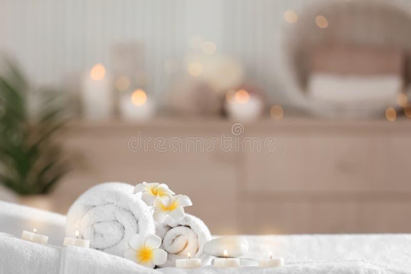 Serviettes et bougies sur la table de massage dans le salon moderne Place pour la relaxation photo stock