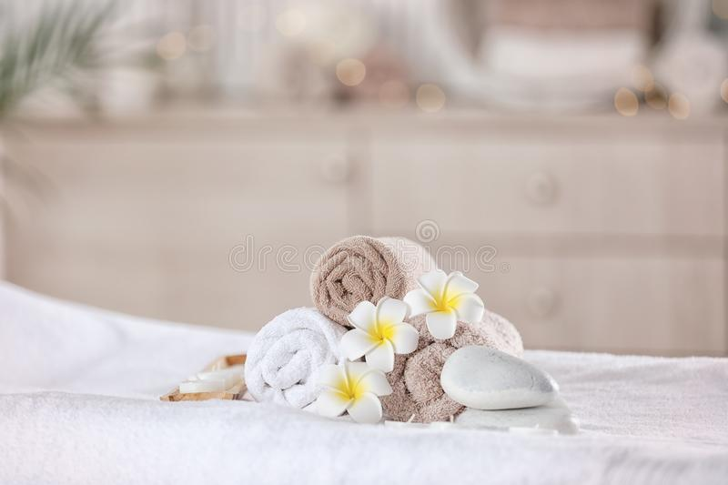 Serviettes et bougies sur la table de massage dans le salon moderne de station thermale Place pour la relaxation photos stock
