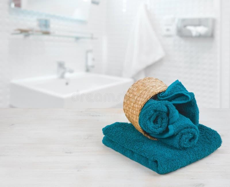 Serviettes pliées vert-bleu dans le panier en osier au-dessus de la salle de bains defocused images stock
