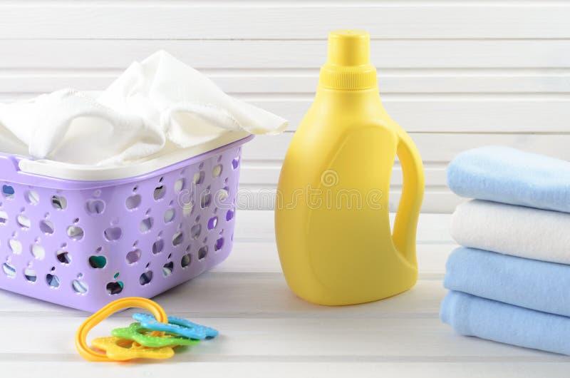 Serviettes sales de bébé dans un panier de blanchisserie pourpre en plastique, fol propre images stock