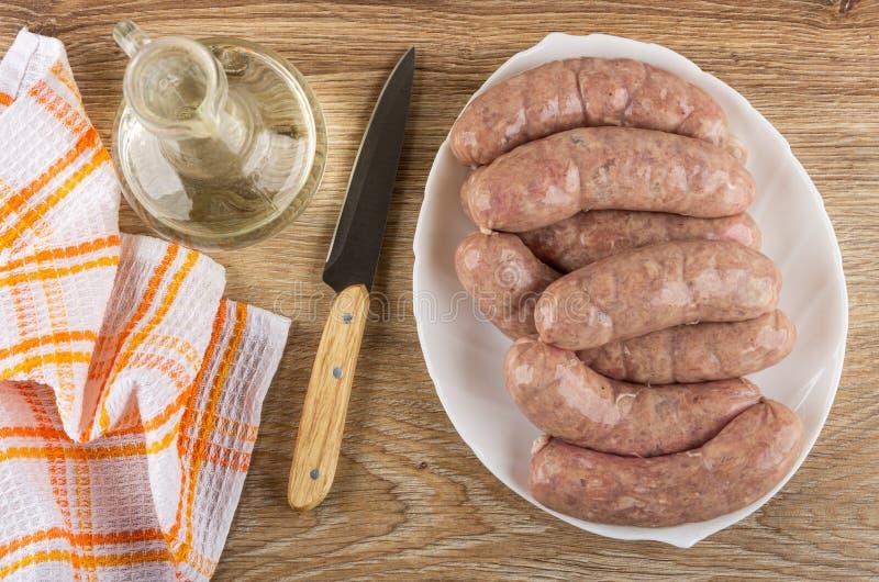 Servilleta, aceite vegetal, cuchillo, salchichas crudas del pollo en cáscara natural en el plato blanco en la tabla Visi?n superi imágenes de archivo libres de regalías