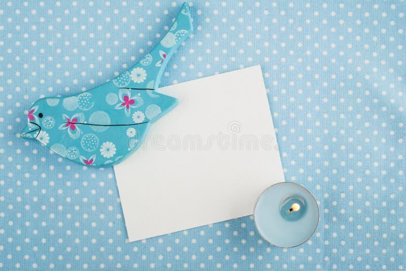 Servilleta azul, tarjeta, pájaro de madera y vela, espacio para el texto fotos de archivo