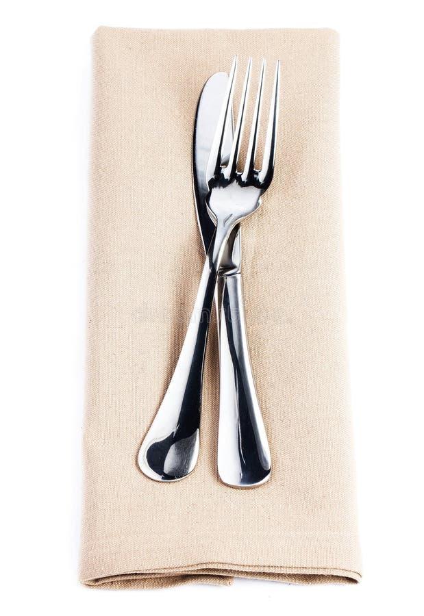 Servilleta de lino con los cubiertos - cuchillo y bifurcación, servicio aislado encendido foto de archivo