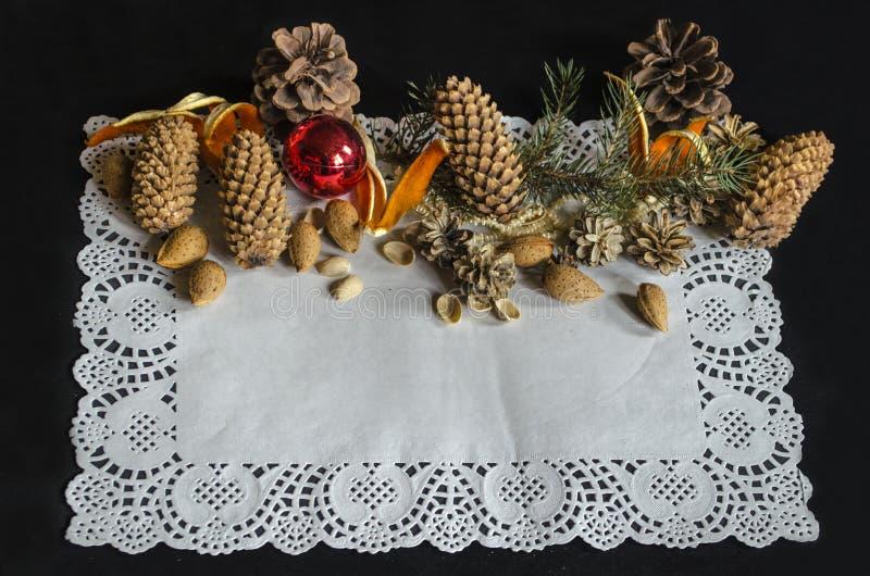 Servilleta de papel cuadrada a cielo abierto con los diversos conos del pino, rama de la picea, juguetes del árbol de navidad, al imagen de archivo