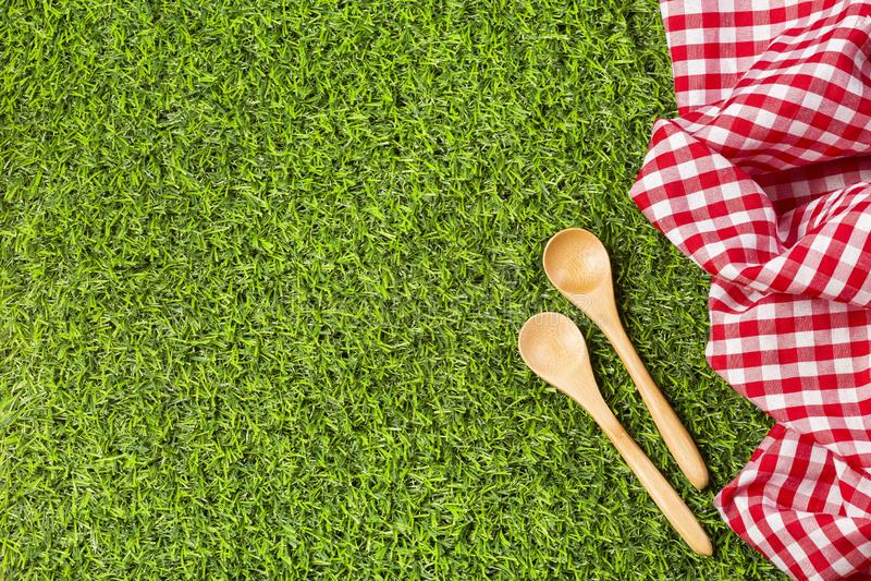 Servilleta roja y cucharas de madera en la hierba verde fotografía de archivo libre de regalías
