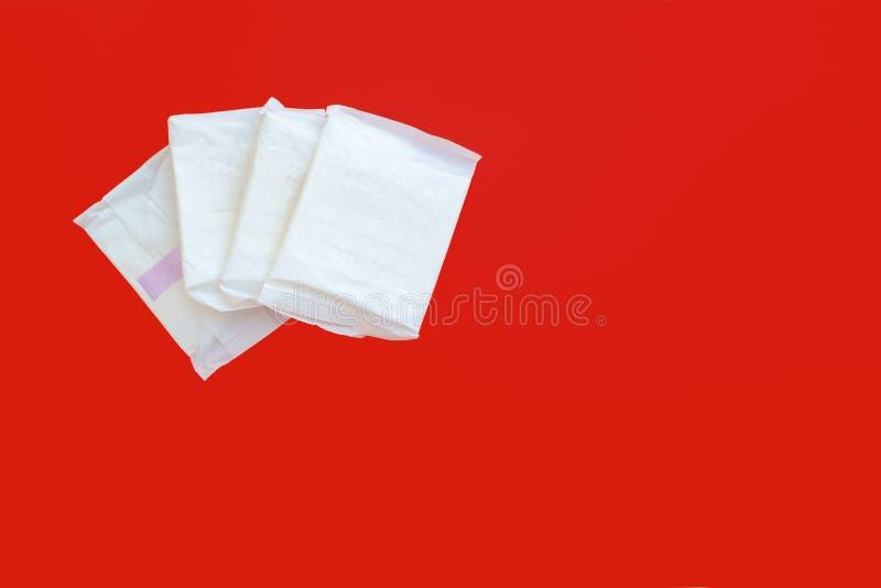 Servilleta sanitaria femenina, un artículo absorbente llevado por una mujer mientras que mestrua, en fondo rojo imagen de archivo
