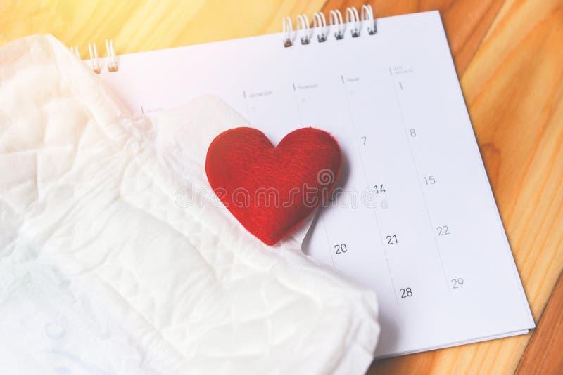 Servilleta sanitaria o cojín sanitario femenino en calendario con el corazón rojo - la higiene femenina significa las hojas absor fotografía de archivo