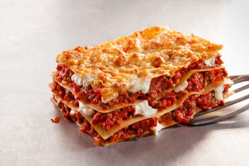Servindo uma parcela de lasanha italiana foto de stock royalty free