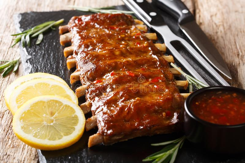Serving BBQ pork ribs with chili sauce and lemon close up on a slate board. horizontal. Serving BBQ pork ribs with chili sauce and lemon close up on a slate stock photo