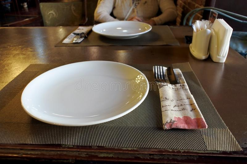 Serving an empty table in a small restaurant. Clean dishes on the table stock images