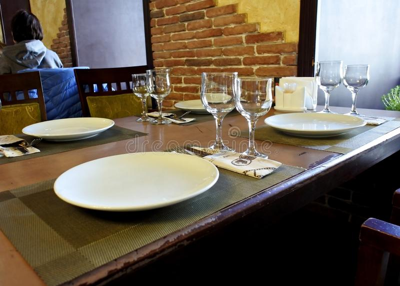 Serving an empty table in a small restaurant. Clean dishes on the table stock image