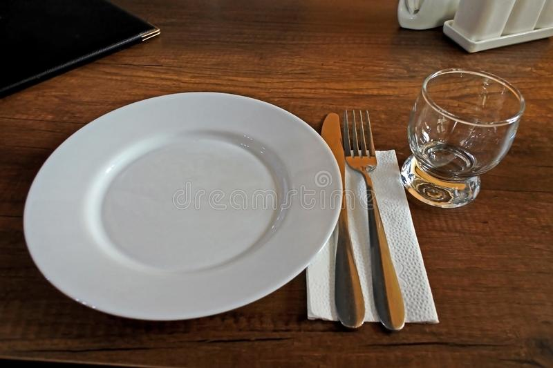 Serving an empty table in a small restaurant. Clean dishes on the table stock photography