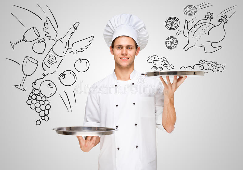 Serving food. Young waiter in a restaurant serving silver trays with sketchy food and drinks to customers for business lunch stock image