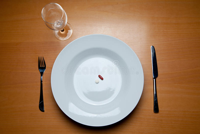 Serving food supplements on wood table. A plate with some pills, cutlery and a wine glass on a wood table stock photography
