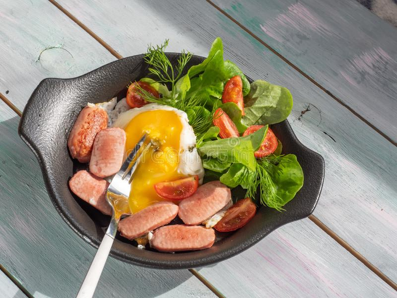 Serving freshly cooked nutritious breakfast of scrambled eggs and sausages, Serving in a black frying pan on a wooden tray. The sun`s rays fall on the royalty free stock photos