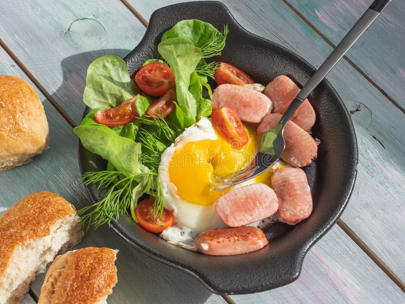 Serving a freshly made nutritious breakfast of scrambled eggs and sausages in a black frying pan with bread buns on a wooden tray. Serving freshly prepared stock photography