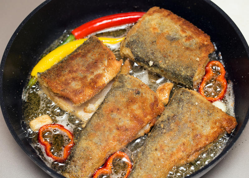 Serving Fried fish in batter in the pan on the hot fat. Trout fried with chili, Close-up of fried fish in a pan with peppers royalty free stock images