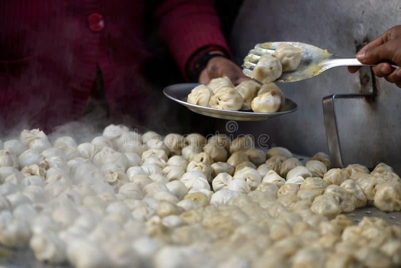 Serving nepalese momos. Serving nepalese dumplings called momos stock photo