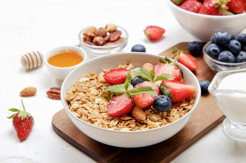 Ceramic granola bowl, assorted ingredients on table. Healthy nutritious breakfast with vegan yogurt, raw fruits, nuts and cereals. royalty free stock photo