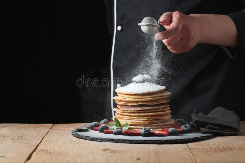 Serving pancakes with powdered sugar and berries. Chef woman han stock photos