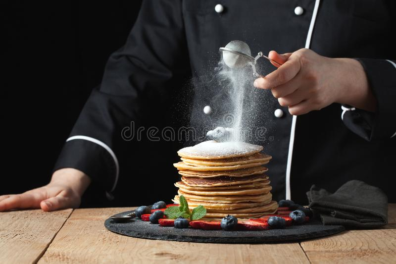 Serving pancakes with powdered sugar and berries. Chef woman hand. Beautiful food still life. slightly toned image, dark black bac royalty free stock image