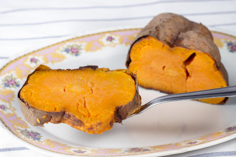 Serving a slice of roasted sweet potato with a pie knife. Slice of roasted sweet potato (Ipomoea batatas) being served with a cake showel from a ceramic white royalty free stock image