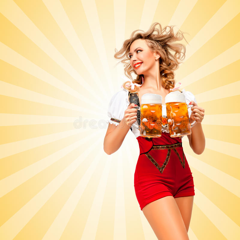 Serving with smile. Beautiful tempting woman wearing red jumper shorts with suspenders as traditional dirndl, serving two beer mugs and looking aside on royalty free stock images